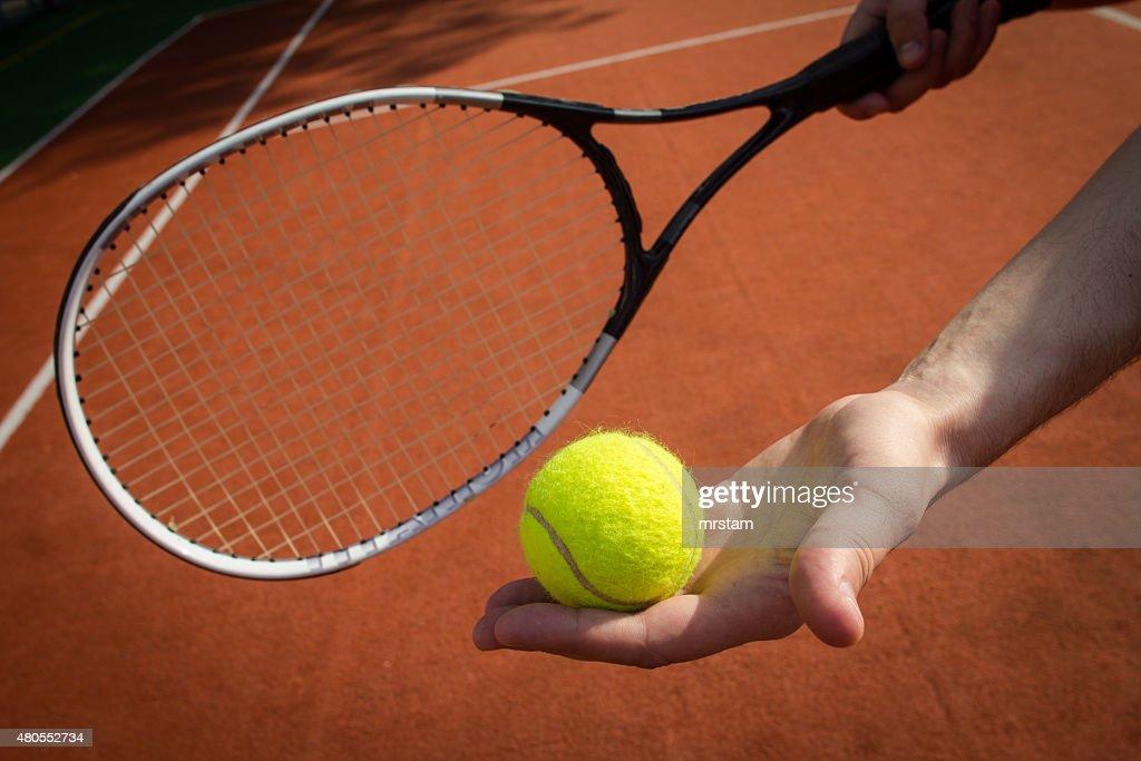 Mano agarrando raqueta de tenis y pelotas en court : Foto de stock