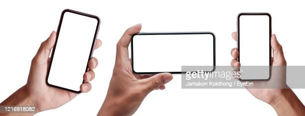 hand holding the black smartphoneand modern frameless design set in rotated positions clipping path - telephone stock pictures, royalty-free photos & images