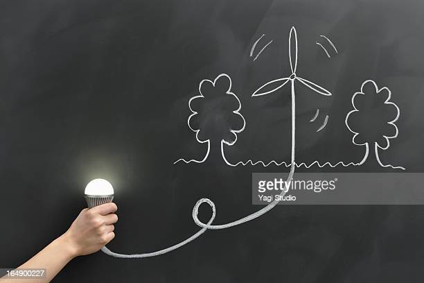 Hand holding the bulb, wind power is drawn on the