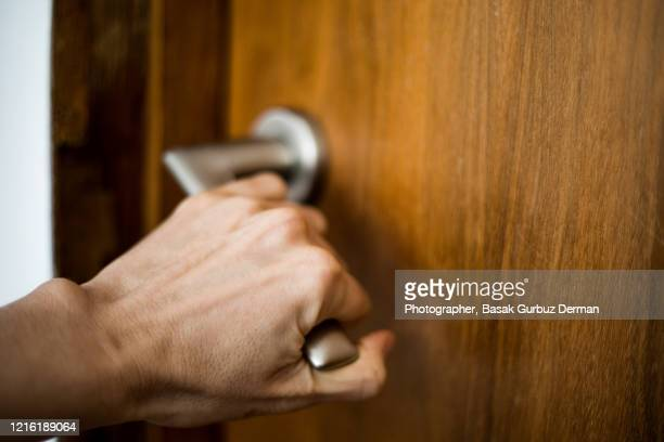 a hand holding the doorknob, opening / closing a door - part of stock pictures, royalty-free photos & images