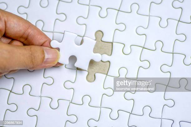 hand holding the last piece of white jigsaw puzzle - final game stock pictures, royalty-free photos & images