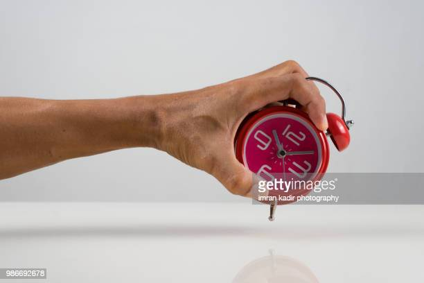 Hand holding the red clock