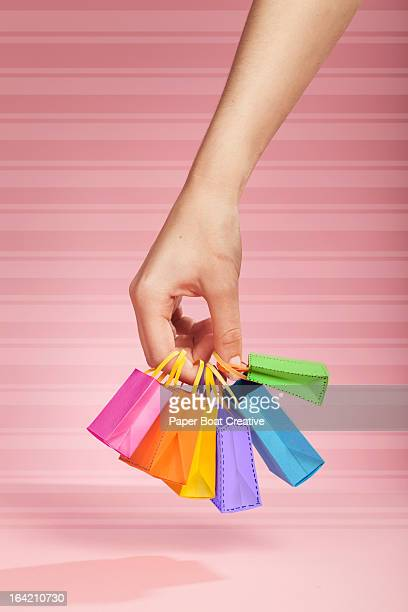 hand holding tiny coloured shopping bags