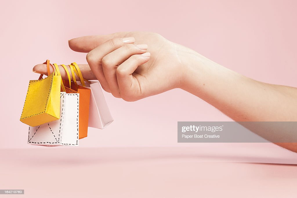 hand holding tiny shopping bags on plain pink : Foto de stock
