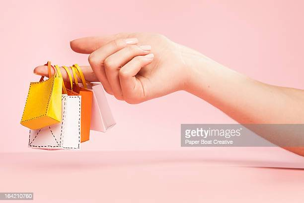 hand holding tiny shopping bags on plain pink - consumentisme stockfoto's en -beelden