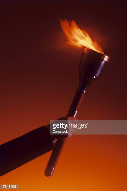 hand holding torch - 聖火トーチ ストックフォトと画像