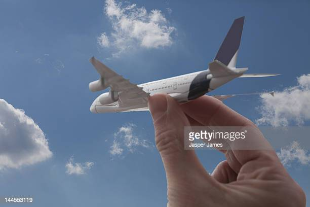 hand holding toy airplane against blue sky
