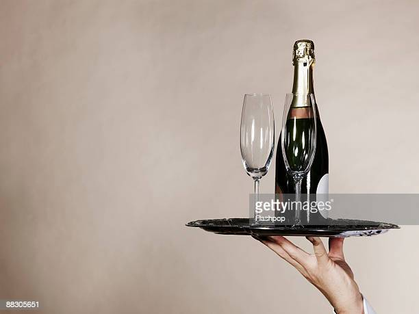 Hand holding tray with champagne and glasses