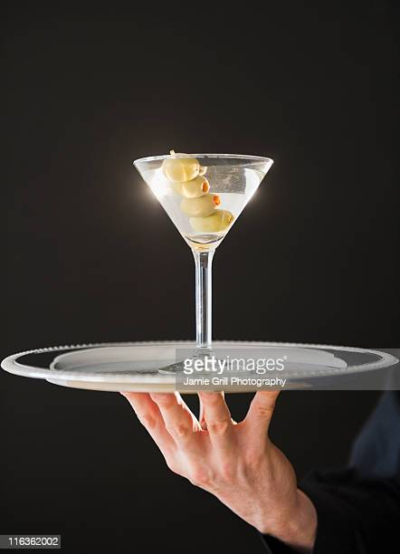 Hand holding tray with martini