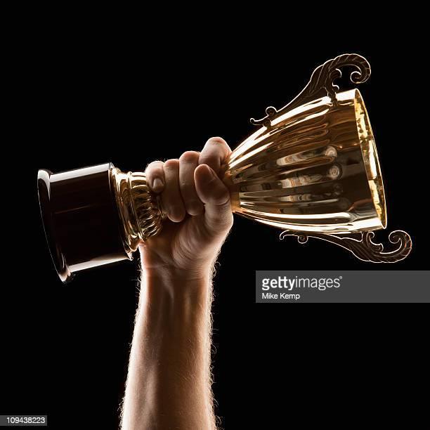 Hand holding trophy on black background