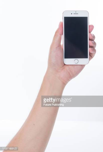 Hand holding up a 2016 Apple iPhone 7 smartphone with a Rose Gold finish, taken on September 22, 2016.