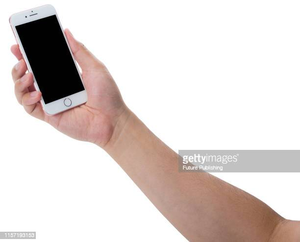 Hand holding up a 2016 Apple iPhone 7 smartphone with a Rose Gold finish taken on September 22 2016