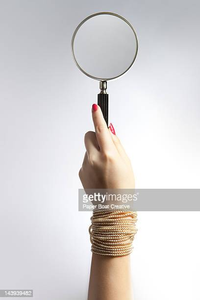 hand holding up a magnifying glass - bracelet stock pictures, royalty-free photos & images