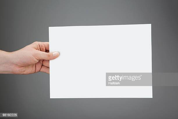A hand holding up a white piece of paper