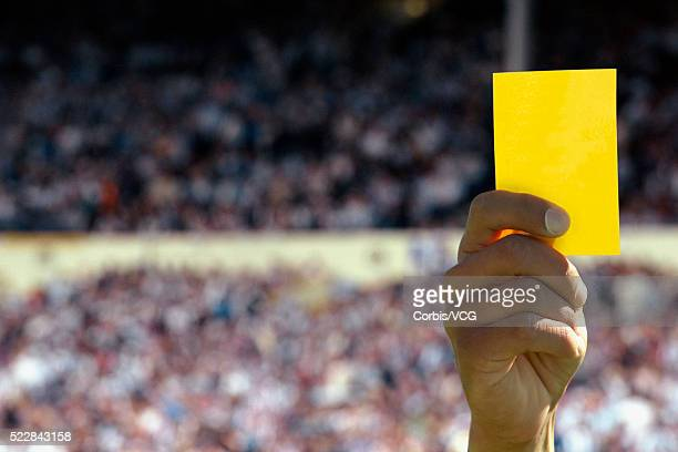 hand holding up a yellow card - yellow card stock pictures, royalty-free photos & images