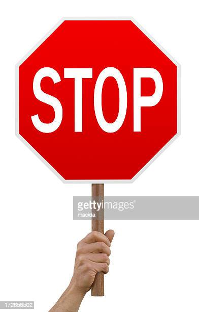 Hand holding up red octagonal stop sign