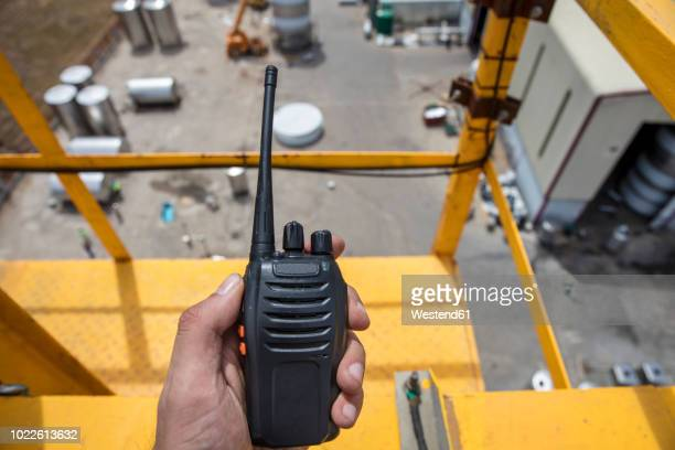 Hand holding walkie talkie on top of a crane on construction site