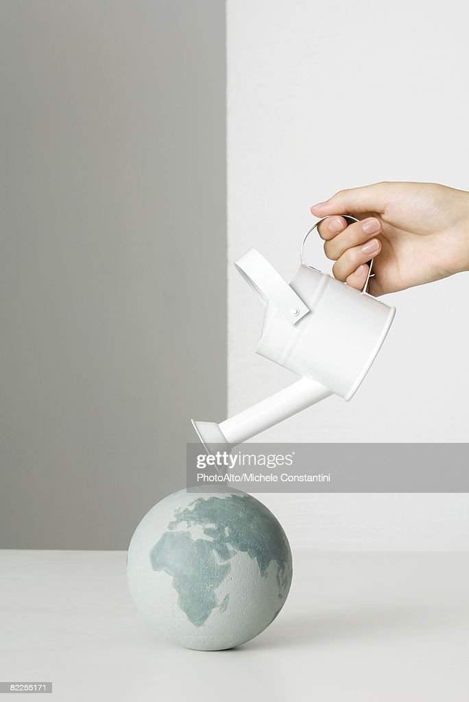 Hand holding watering can over globe : Stock Photo