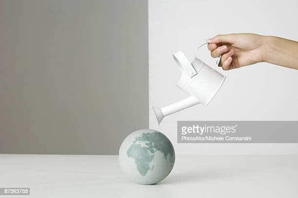 hand holding watering can over small globe - world kindness day fotografías e imágenes de stock