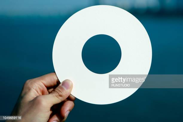 Hand holding white blank circle card