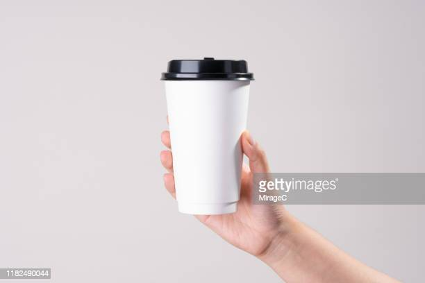 hand holding white paper cup - coffee cup stock pictures, royalty-free photos & images