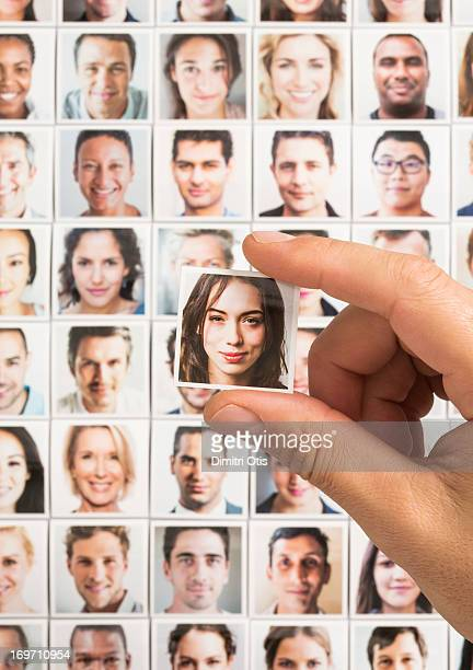 Hand holding woman's portrait above grid of others