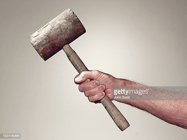 Hand holding wooden mallet