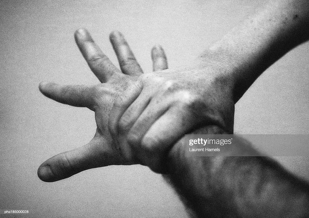 Hand holding wrist, close-up, b&w : Stockfoto