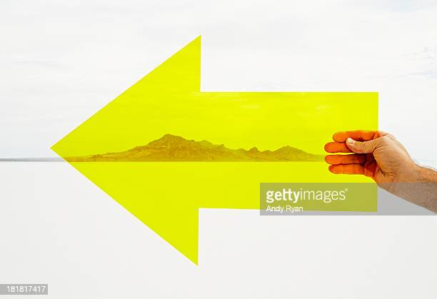Hand holding yellow arrow in desert.