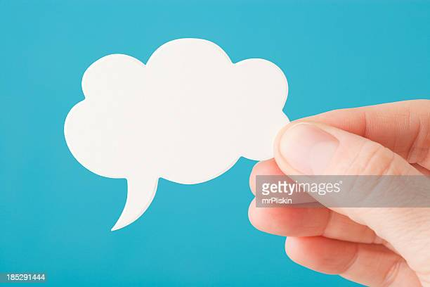Hand holds a blank white speech bubble