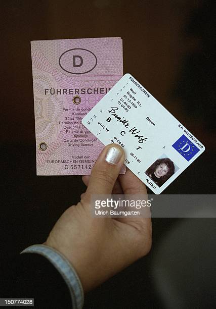 A hand holds a classical EU driving license and an EU driving license in cheque card format