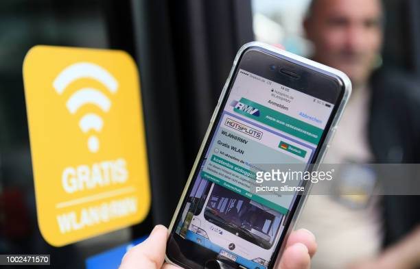 ILLUSTRATION A hand holds a smartphone next to the sticker on a bus showcasing the internet usage at the airport of Frankfurt am Main Germany 11 May...