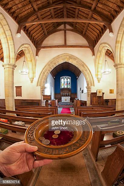 A Hand Holds An Offering Plate At The Back Of A Church; Northumberland England