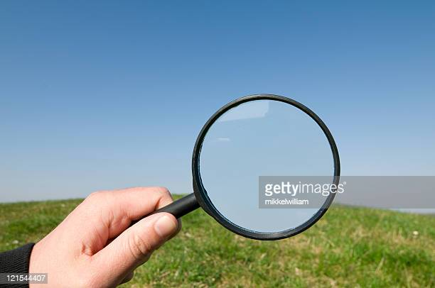 Hand holds magnifying glass up op a hill and sky