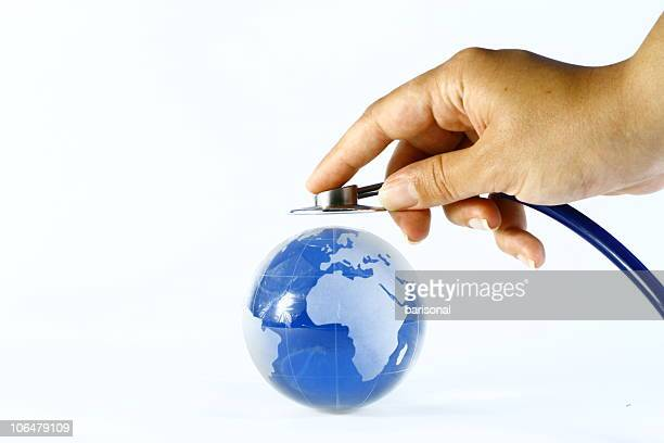 hand holds stethoscope up to world globe global healthcare - world health organization stock pictures, royalty-free photos & images