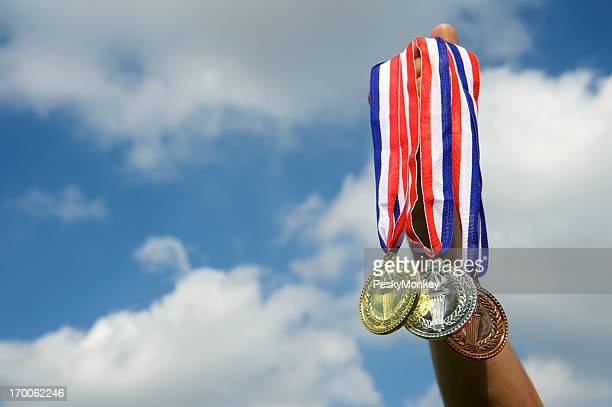 Hand Holds Up Gold Silver Bronze Medals in Sky