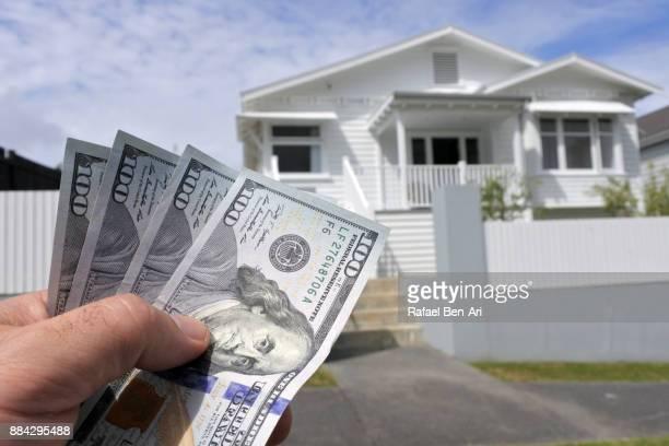 hand holds us dollar bills against a north american house - rafael ben ari stockfoto's en -beelden