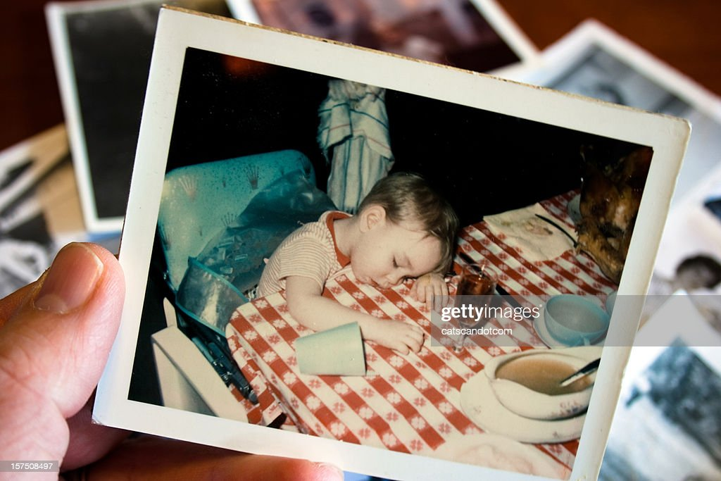 Hand holds Vintage photograph of boy at thanksgiving : Stock Photo