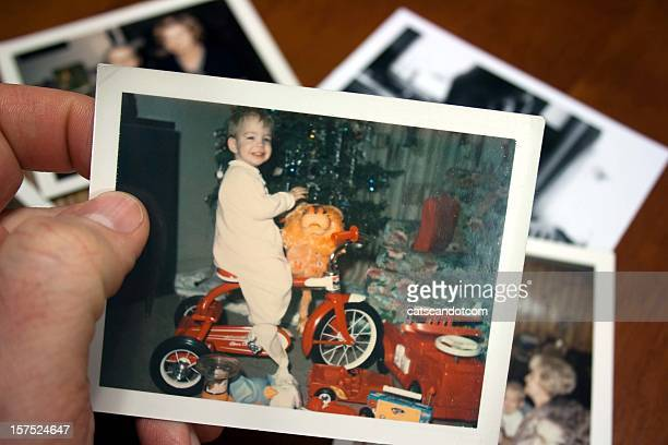 hand holds vintage photograph of boy on tricycle at christmas - foto stockfoto's en -beelden