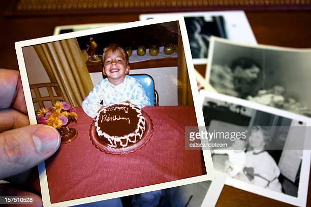 Hand holds Vintage photograph of child and birthday cake