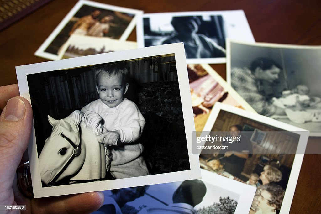 Hand holds Vintage photograph of child with hobby horse toy : Stock Photo