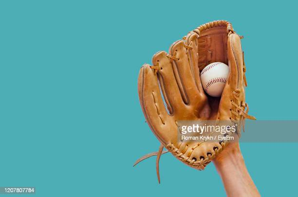 hand in a leather baseball glove catches a white ball in defocus on a red background - baseball glove stock pictures, royalty-free photos & images