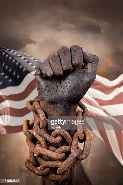 Hand in chains with US flag behind