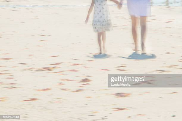 Hand in hand, mother and daughter on beach