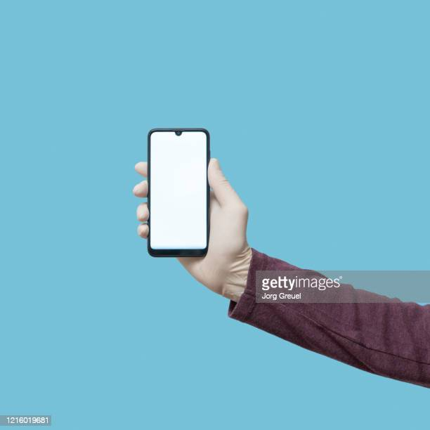 hand in latex glove holding a smartphone - long sleeved stock pictures, royalty-free photos & images