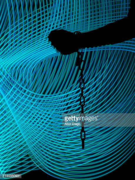 hand in motion making strength with a hanging chain. it could be the release of a prisoner or the fight for freedom and human rights. - human trafficking stock pictures, royalty-free photos & images