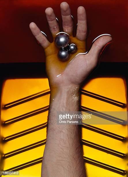 Hand in oil holding ball bearings