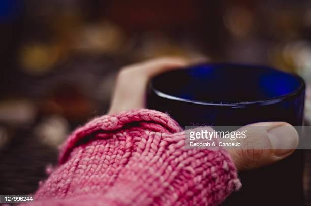 Hand, in pink fingerless mitt, with mug