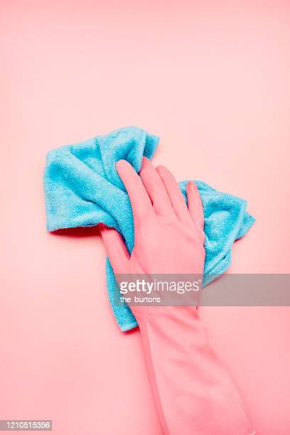 hand in pink glove with blue cleaning rag on pink background, house cleaning - hygiene stock-fotos und bilder