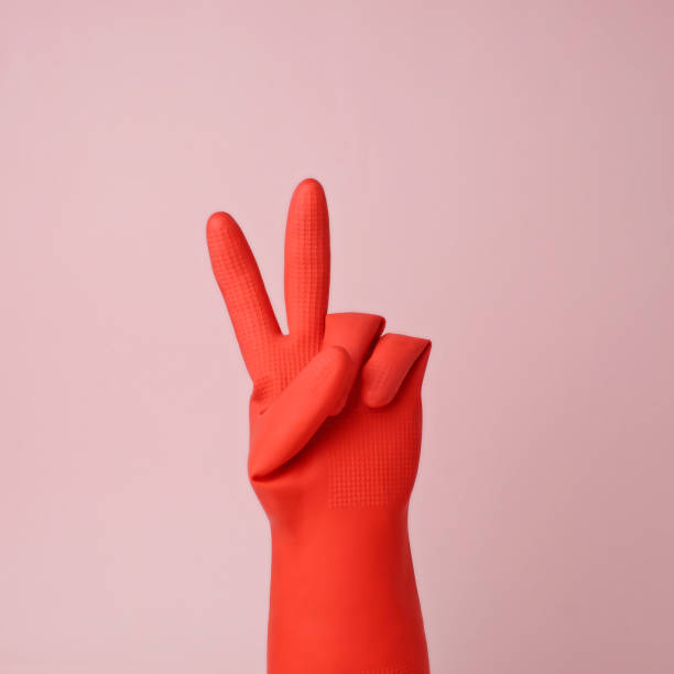Hand in red rubber glove making peace sign